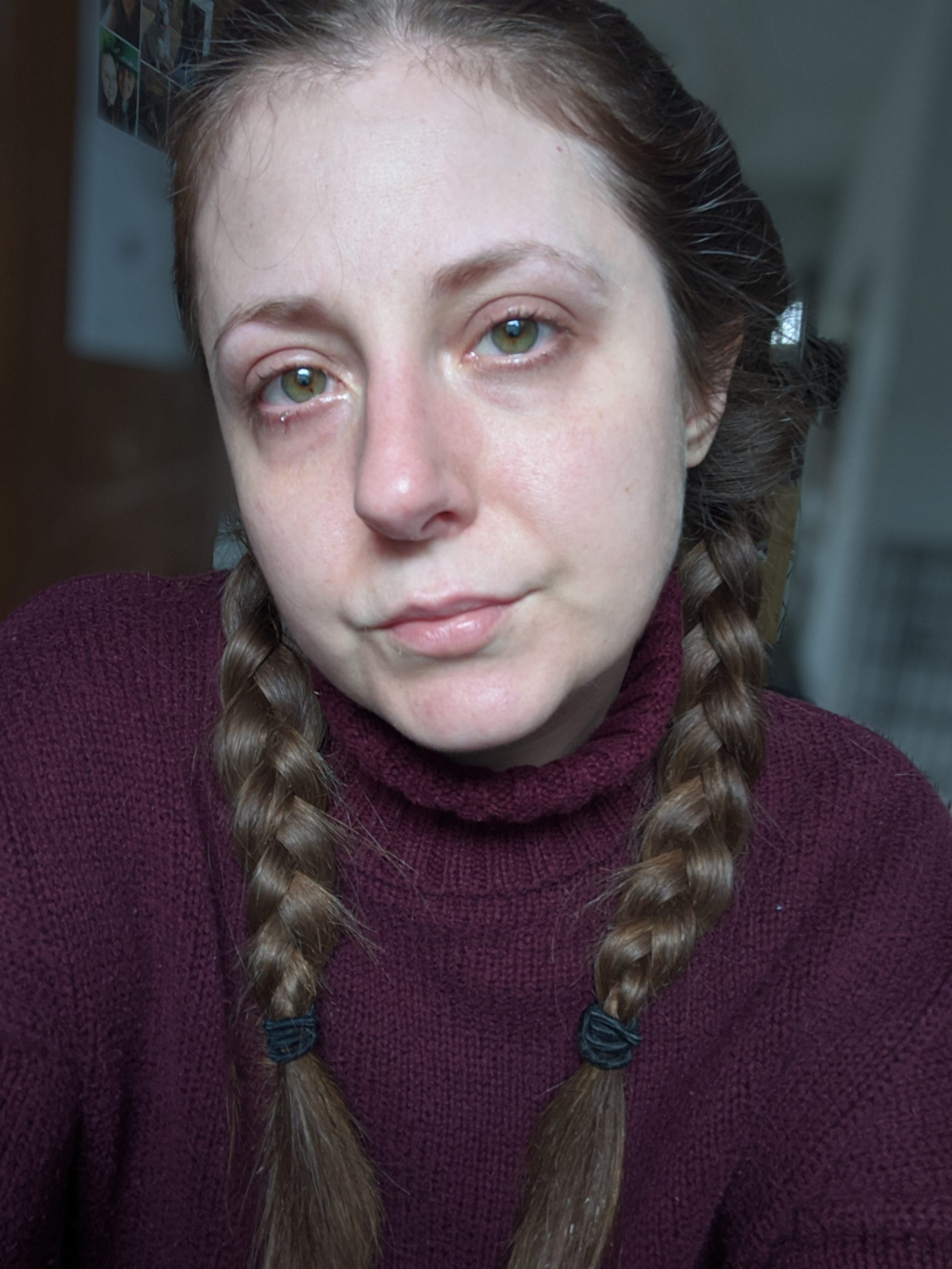 Brianna McInerny wearing a burgundy turtle neck with her hair in braids, with tears in her red eyes.