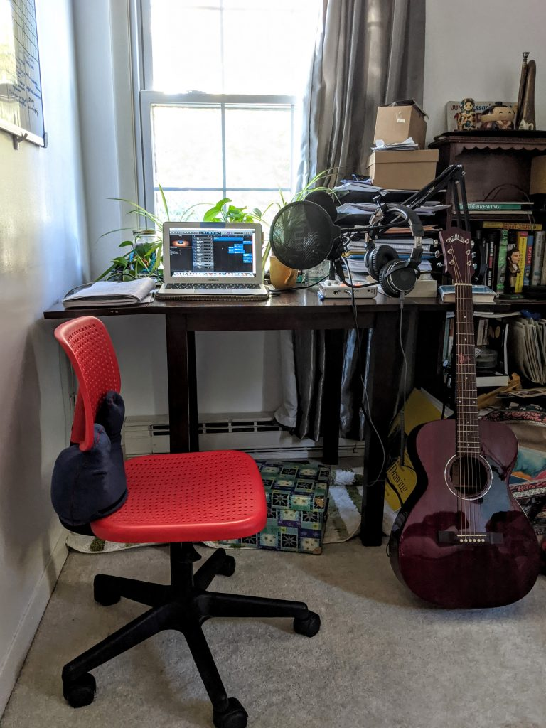 Brianna's office desk with a red chair, an acoustic guitar, and several plants