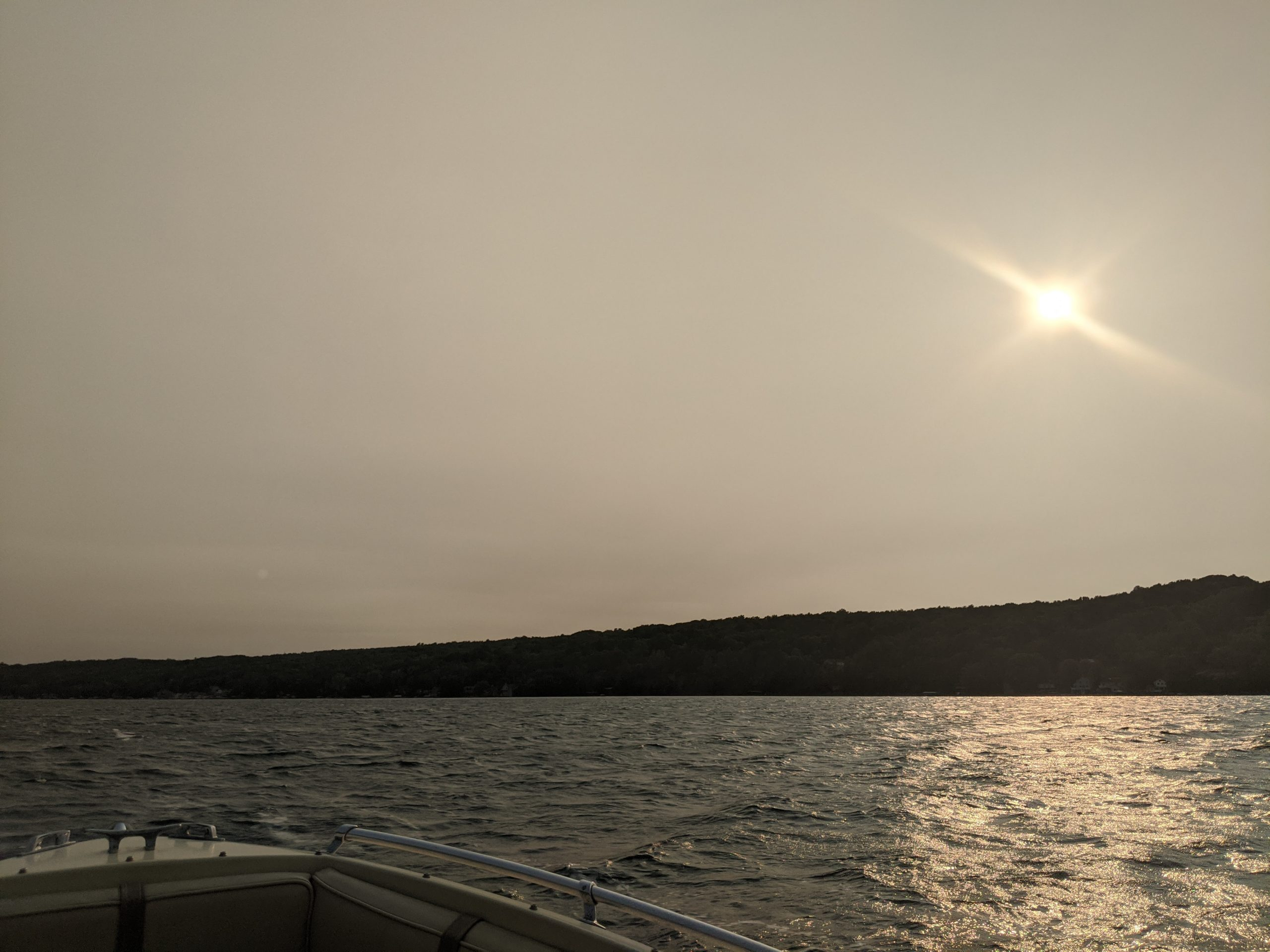 Smoky view of the lake with the sun glimmering in the dark gray sky